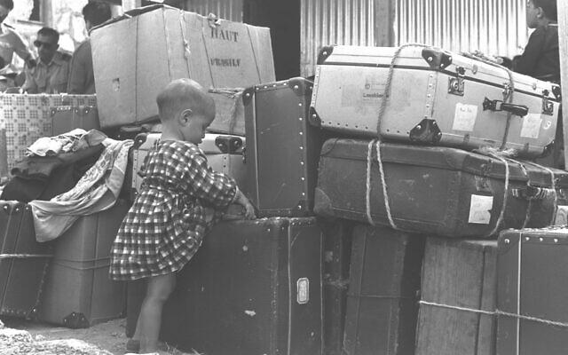 Un enfant juif immigré de Casablanca avec des bagages à l'aéroport de Lod, le 24 septembre 1955.