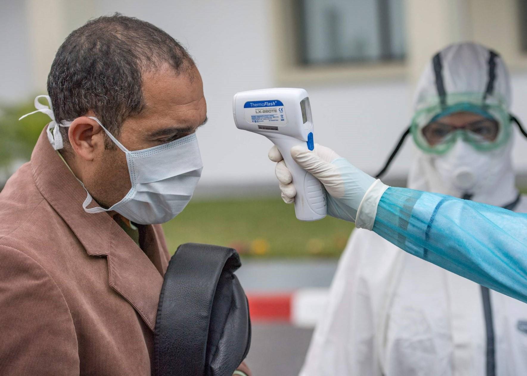 Un agent de santé prend la température d'un patient à l'hôpital militaire Mohamed V de Rabat. © AFP