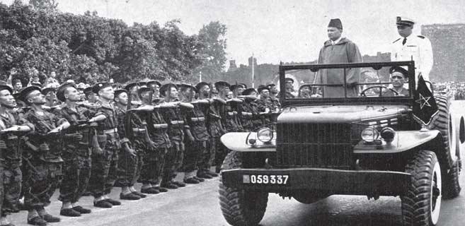 Feu Mohammed V passant en revue les premiers éléments des FAR, le 15 mai 1956 à Rabat, en compagnie du Prince héritier Moulay El Hassan, futur Hassan II.